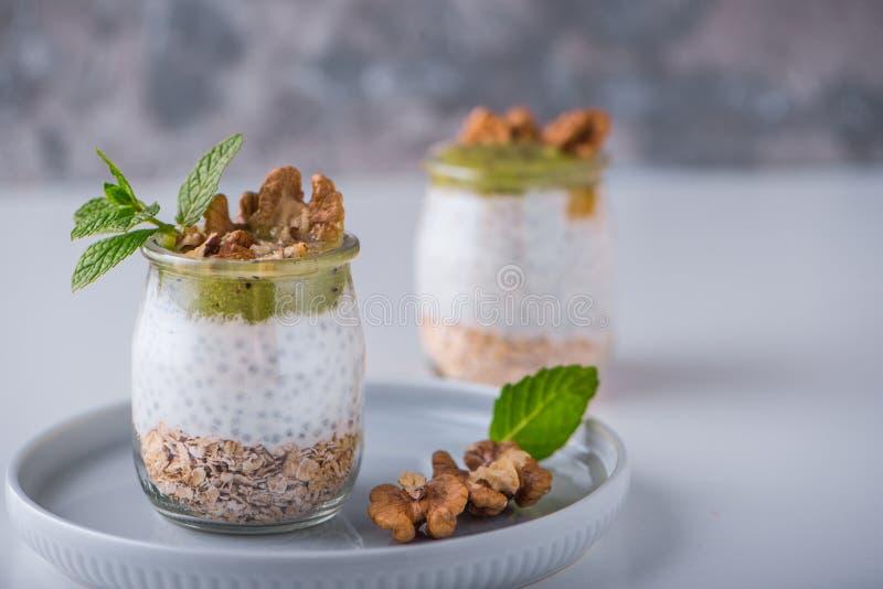 Домодельный пудинг семян Chia и молока миндалины с хлопьями и пюрем кивиа с грецкими орехами и мятой в стеклянных опарниках Vegan стоковые изображения