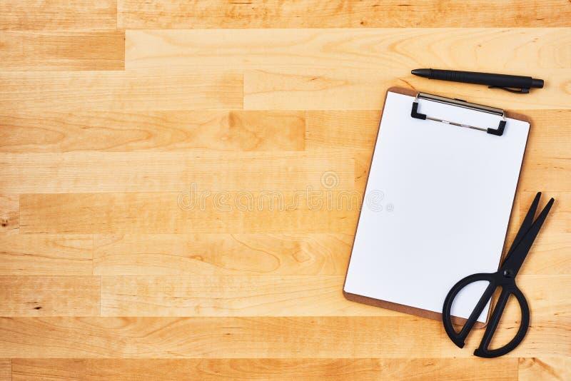 Доска сзажимом для бумаги, ножницы и ручка картона на деревянной предпосылке стоковое изображение