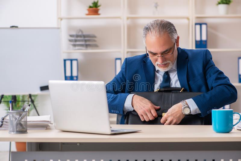 Достигший возраста мужской работник работая в офисе стоковые фотографии rf