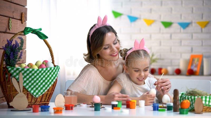 Дочь матери уча украшает яйца, семью в милом держателе сидя на таблице стоковые изображения rf