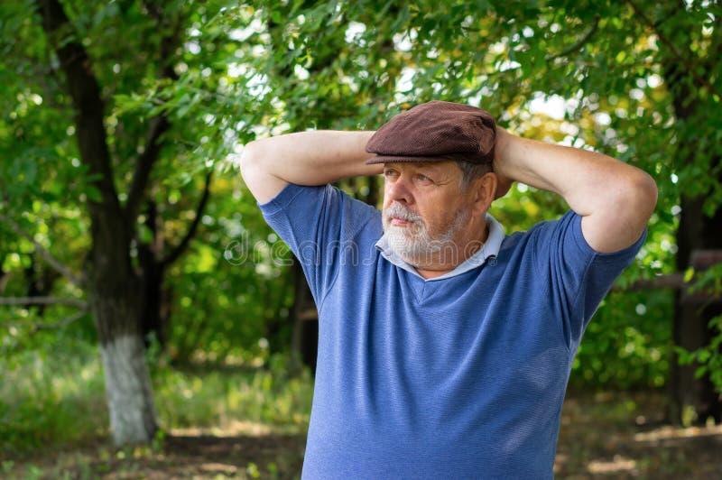 Ð-ortrait de l'homme supérieur barbu se reposant dans l'ombre d'arbre photos stock
