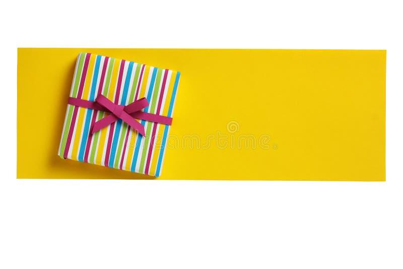 Ð ¡ prezenta olorful pudełko na koloru żółtego papieru listu pustym miejscu fotografia stock