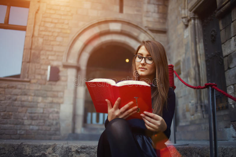 Ð  ttractive女孩读了引人入胜的书美好的晴天 库存图片