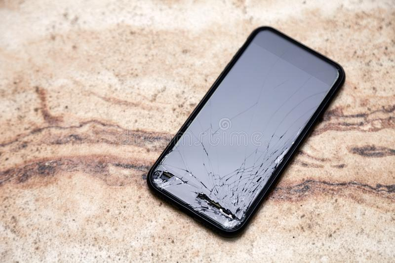 Smartphone With A Broken Screen On A Wooden Background Stock Photo