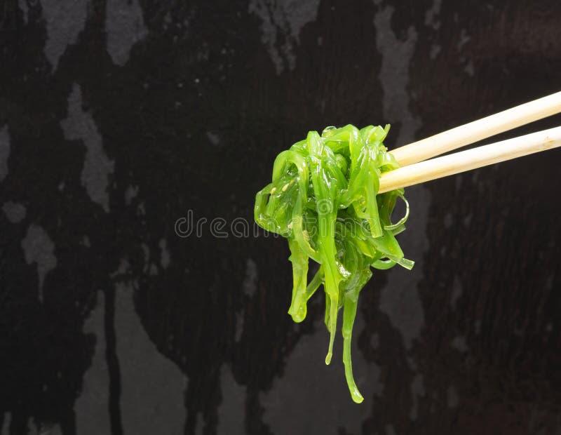 Салат морской водоросли на черноте Палочки и салат chuka стоковое фото