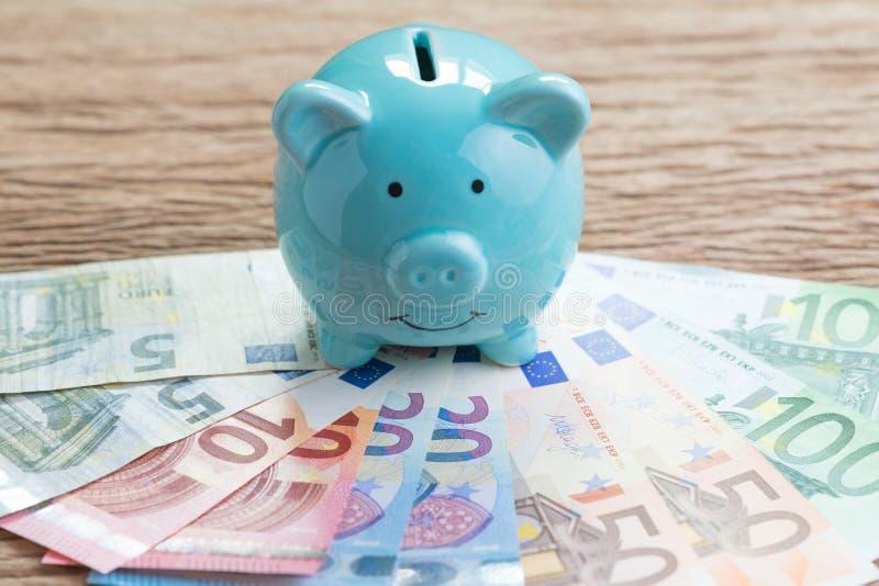 Сберегательный счет денег финансов, концепция экономики Европы, голубая копилка на куче банкнот евро на деревянном столе, будущем стоковые изображения rf
