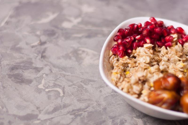 Сваренные yummy теплые овсяная каша и куча зрелых свежих семян гранатового дерева и серия высушенных дат в белом керамическом шар стоковые фото