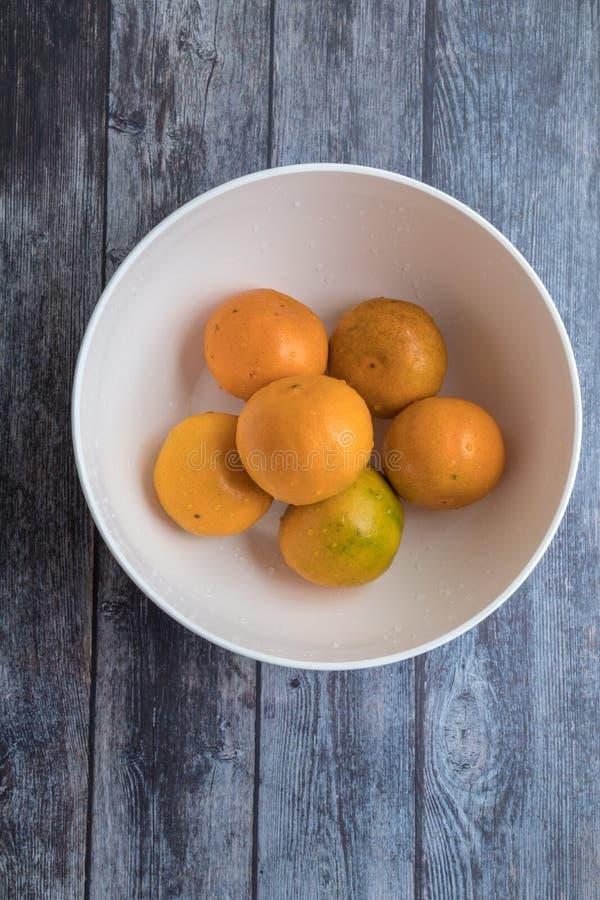 Свежие апельсины в белом шаре на предпосылке деревянного стола стоковое фото rf