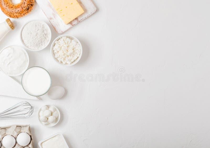 Свежие молочные продучты на белой предпосылке таблицы Стекло молока, шара сметаны и творога и яичек свежая испеченная bagel стоковые фото