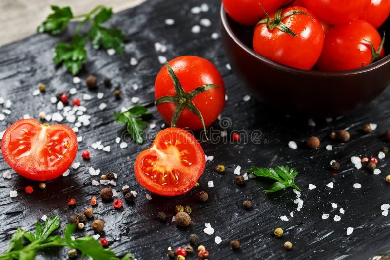 Свежие отрезанные томаты вишни на черной предпосылке со специями грубым солью и травами Взгляд сверху, польза как варить ингредие стоковая фотография rf