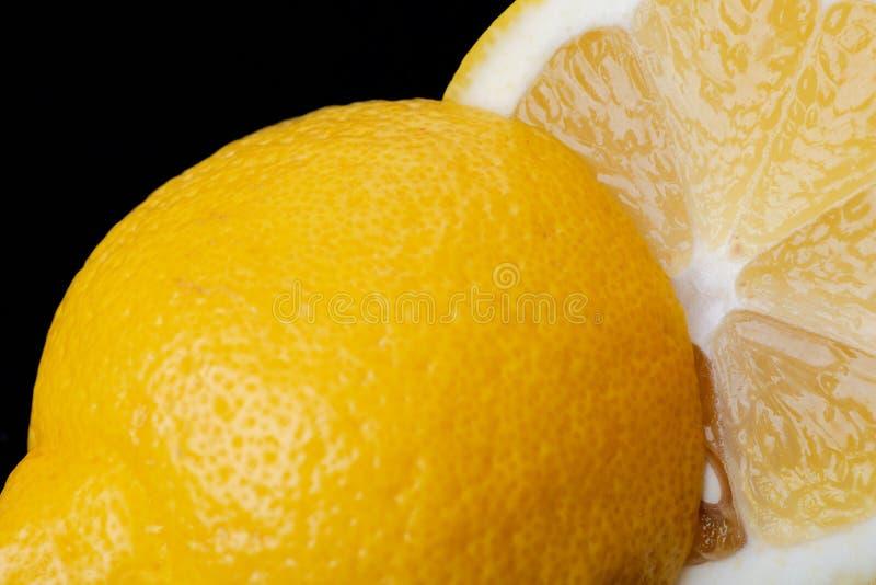 Свежий зрелый органический отрезок лимона в половине изолированный на черноте Citrus Limon Семья рутовые стоковая фотография rf