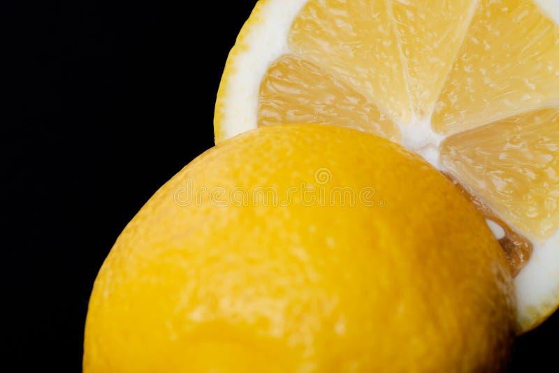 Свежий зрелый органический отрезок лимона в половине изолированный на черноте Citrus Limon Семья рутовые стоковое изображение