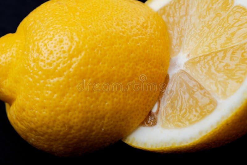 Свежий зрелый органический отрезок лимона в половине изолированный на черноте Citrus Limon Семья рутовые стоковое изображение rf