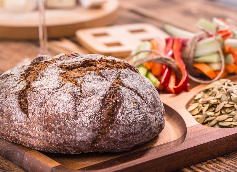 Свежий круг темного хлеба на деревянной плите стоковая фотография rf