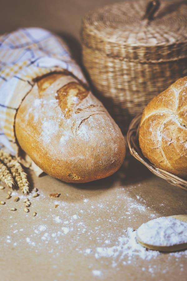 Свежо испекл хлеб, пшеницу и муку на деревенской предпосылке стоковые изображения