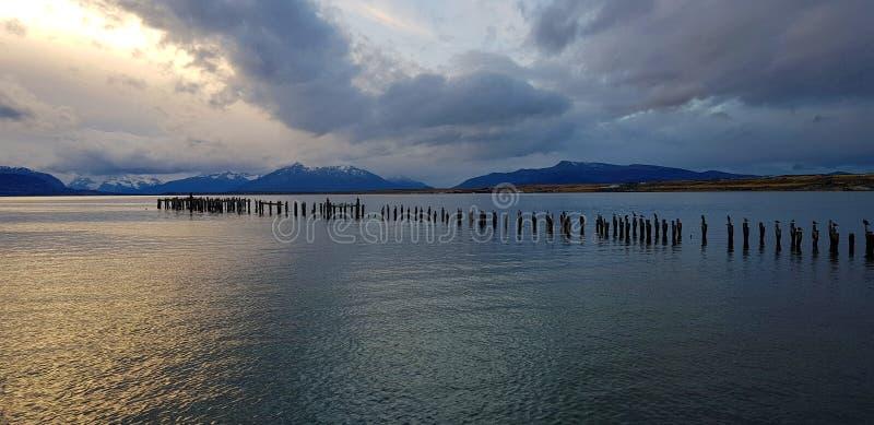 Света захода солнца над остатками пристани, Puerto Natales, Чили стоковые фотографии rf