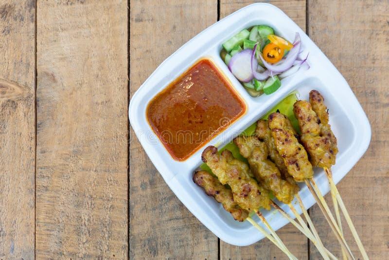 Свинина Satay зажарила свинину, который служат с соусом арахиса или сладким и кислым соусом, Тайской кухней на деревянной таблице стоковое изображение