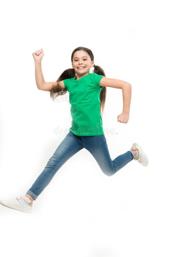 свободный скакать Прелестная маленькая девочка с длинными волосами брюнета Небольшой ребенок нося случайный стиль моды Небольшая  стоковая фотография