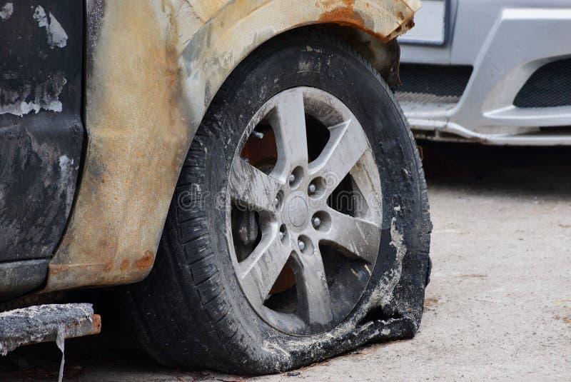 Сгорели спущенная шина на автомобиле на серой дороге асфальта стоковые фото