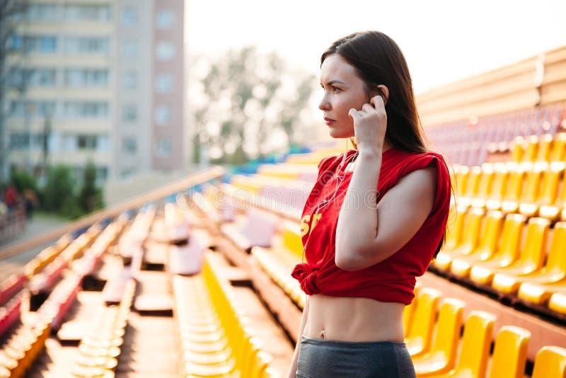 Сексуальная девушка спорта представляя на стадионе nad слушая музыку на наушниках Девушка фитнеса с диаграммой спорт в гетры и кр стоковое изображение rf