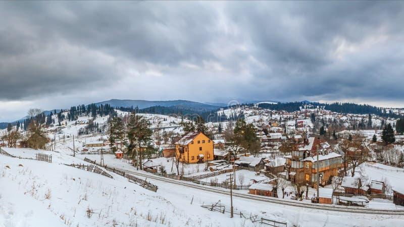 Сельский ландшафт зимы - взгляд деревни Vorokhta с железной дорогой в реке Prut долины прикарпатские горы стоковые фотографии rf