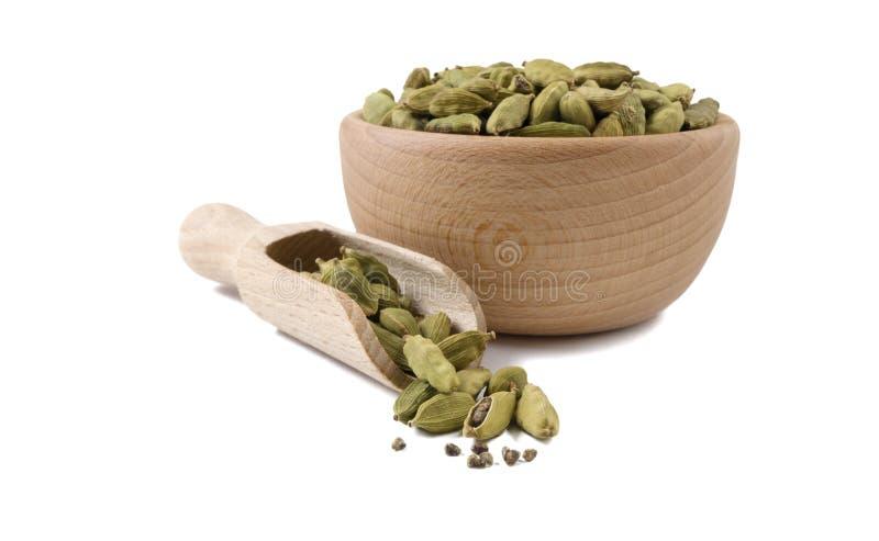 Семена Cardamon в деревянном шаре и ветроуловителе изолированных на белой предпосылке Специи и пищевые ингредиенты стоковая фотография