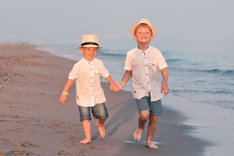 Семья идя на пляж вечера во время захода солнца 2 брать в соломенных шляпах стоковые изображения rf