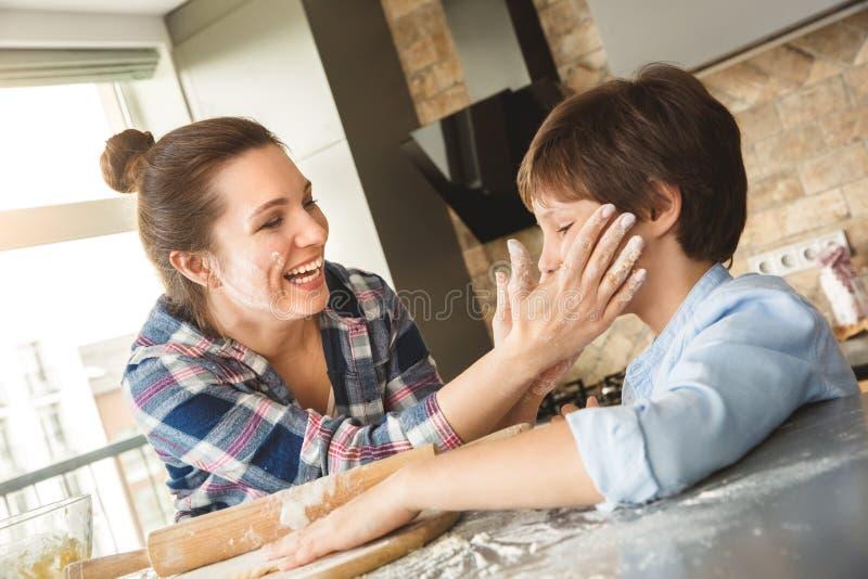 Семья дома стоя на таблице в матери кухни совместно держа сторону сына с floured концом-вверх рук жизнерадостным стоковая фотография