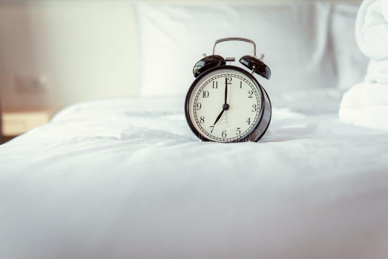 Сетноой-аналогов будильник на спальне в современном доме, ретро таймере на 7 00 a M на белой кровати крышки стоковые изображения