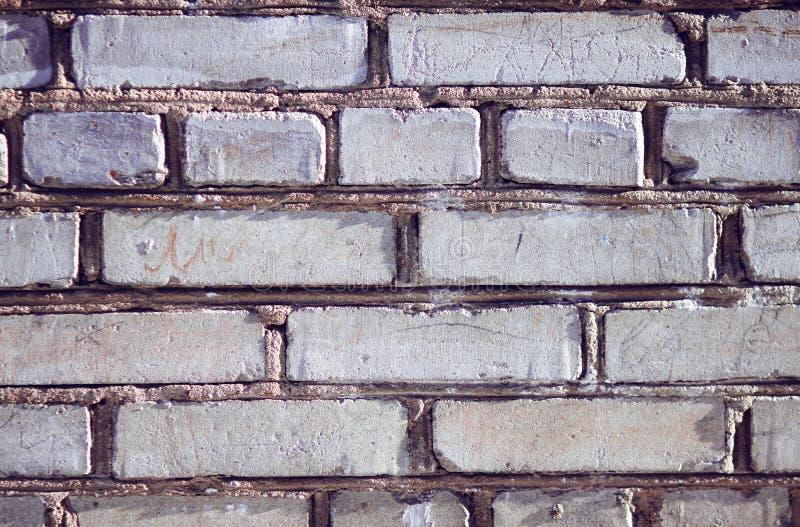 Серая стена здания, построенная грубых неровных кирпичей стоковые изображения