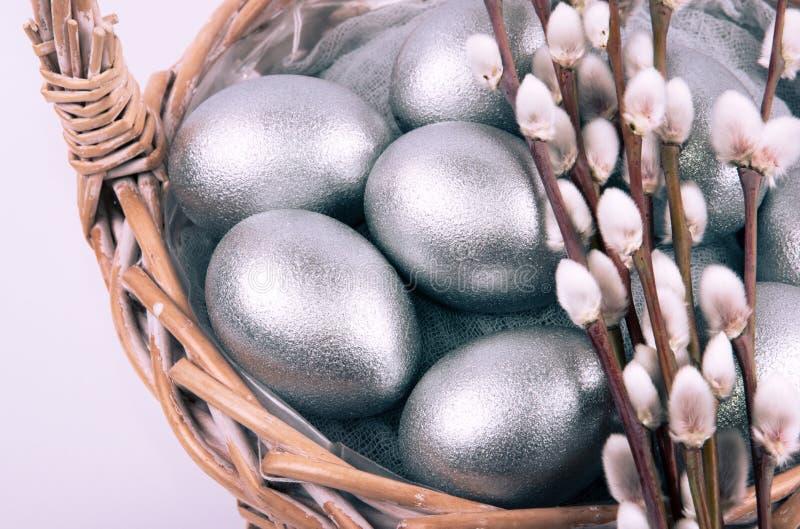 Серебряные покрашенные пасхальные яйца в плетеной корзине с концом-вверх ветвей catkins вербы установьте текст стоковое фото rf