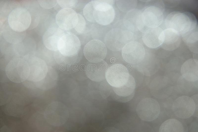 Серебряное блестящее bokeh светов рождества абстрактная запачканная предпосылка стоковое фото rf