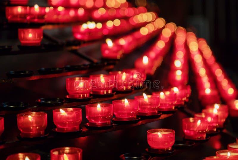 Серии гореть красные свечи в церков стоковые изображения