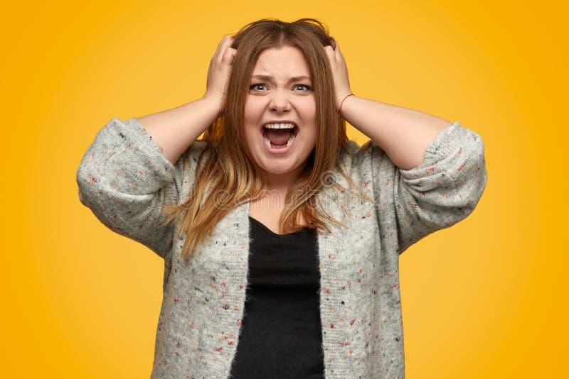 Сердитая полная женщина кричащая и срывая вне волосы стоковое фото rf