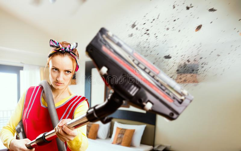 Сердитая домохозяйка в рисберме с пылесосом стоковое фото rf