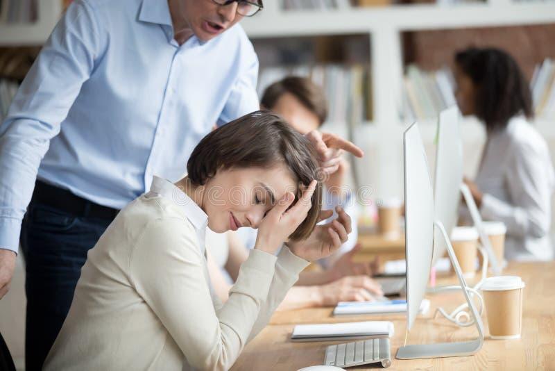 Сердитый раздражанный CEO (главный исполнительный директор) компании делая выговор женщина работника стоковые фотографии rf