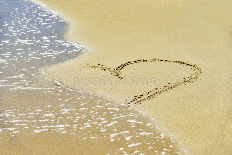 Сердце на песке помыто прочь волнами на береге стоковое изображение rf