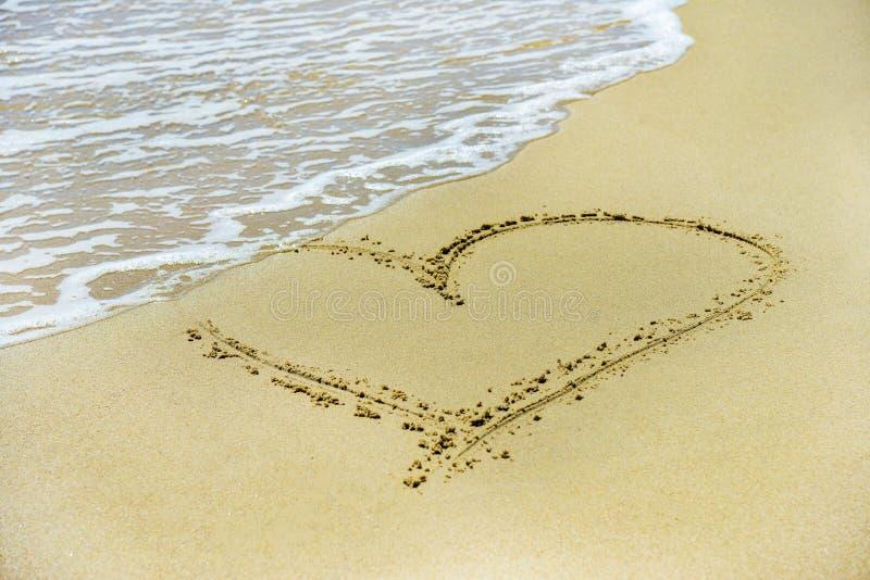 Сердце на песке помыто прочь волнами на береге стоковая фотография rf