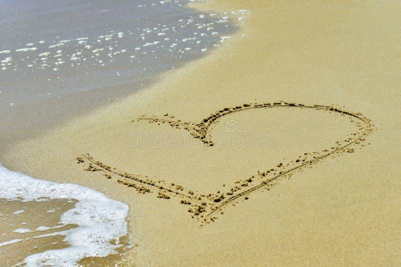 Сердце на песке помыто прочь волнами на береге стоковое изображение