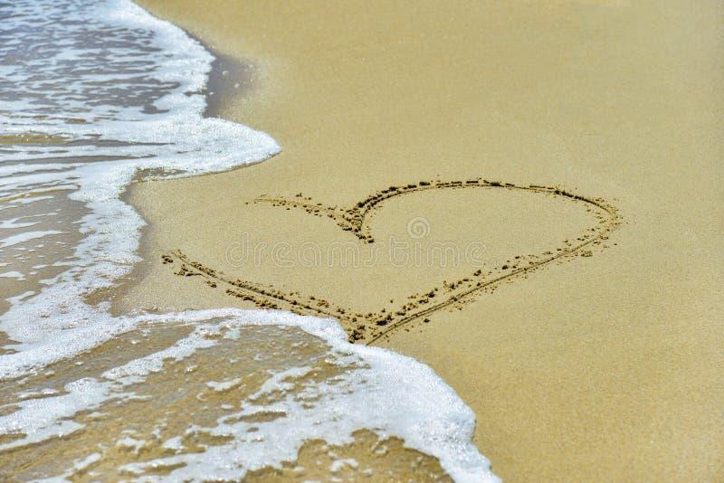 Сердце на песке помыто прочь волнами на береге стоковое фото