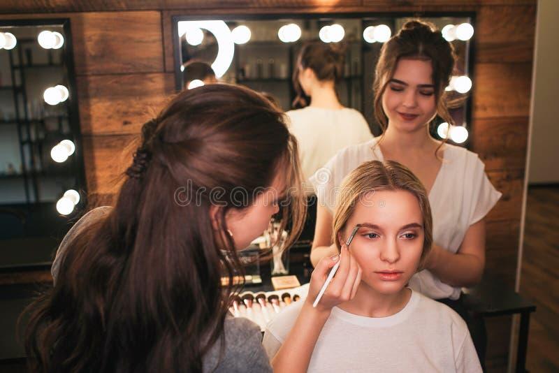 Серьезная белокурая женщина сидит на стуле в комнате красоты Художник макияжа положил некоторый цвет на чела Sstand парикмахера п стоковое изображение