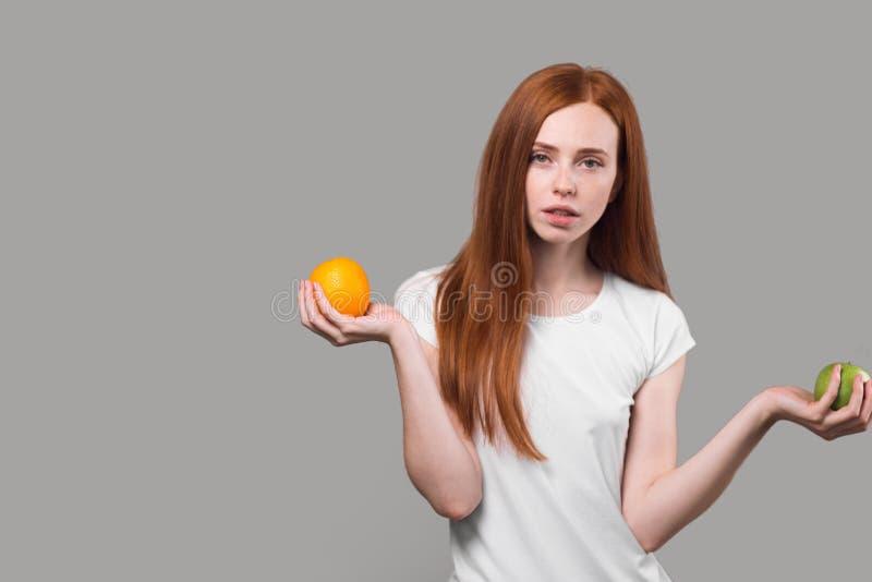 Серьезная тонкая девушка в белой футболке держа апельсин и яблоко стоковые фотографии rf