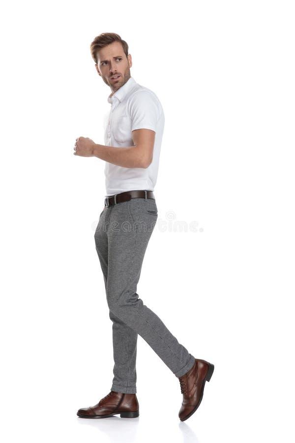 Серьезные или потревоженные молодые случайные прогулки и взгляды человека назад стоковое изображение rf