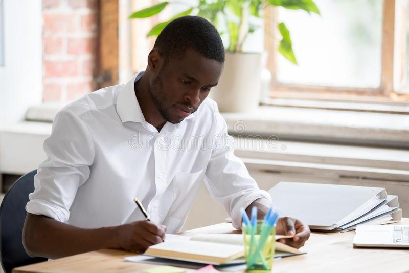 Серьезный африканский студент университета человека изучая учебник чтения делая примечания стоковое фото