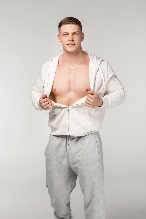 Серьезный сильный, мышечный человек в сером sportswear стоковое изображение rf