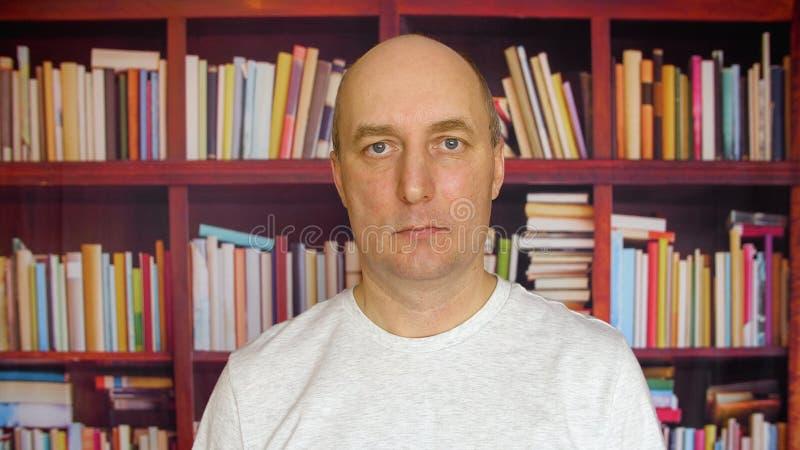 Серьезный человек в библиотеке Близкий поднимающий вверх человек взгляда с лысой головой перед книжными полками в портрете библио стоковая фотография