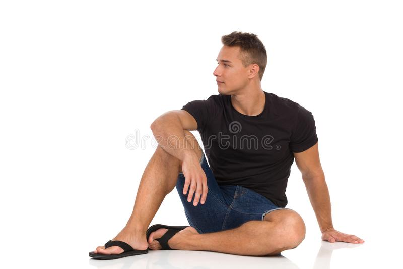 Серьезный человек сидеть расслабленный на поле и смотреть прочь стоковые изображения rf