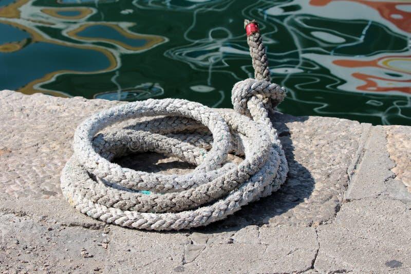Сильная белизна тяжело - используемая веревочка вышла на край каменной пристани рядом со штилем на море с маслообразным отражение стоковая фотография