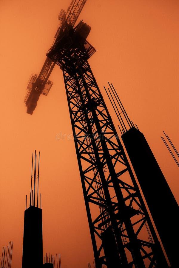 Силуэт крана башни и столбца бетона армированного стоковое изображение