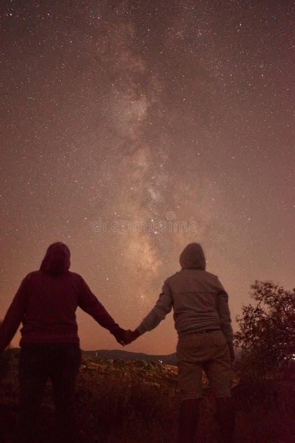Силуэт креста вечером с красивым backgroundSilhouette млечного пути человека и женщины в любов держа руки с beautif стоковое фото